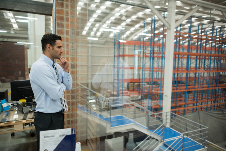 Man looks out into warehouse space.
