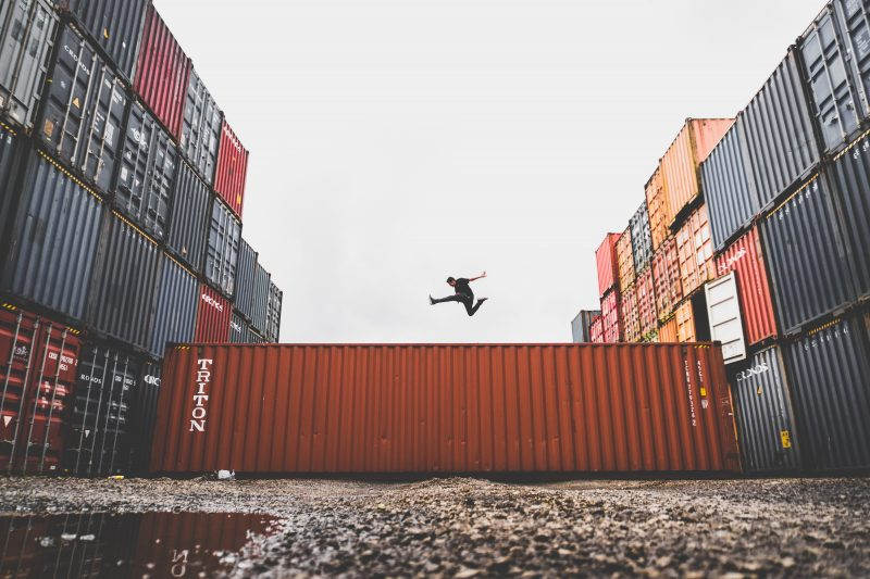 Man jumping off of shipping container with more containers in background