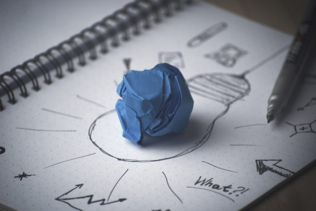 A piece of paper with brainstorming on it, and a crumpled up blue piece of paper in the middle.