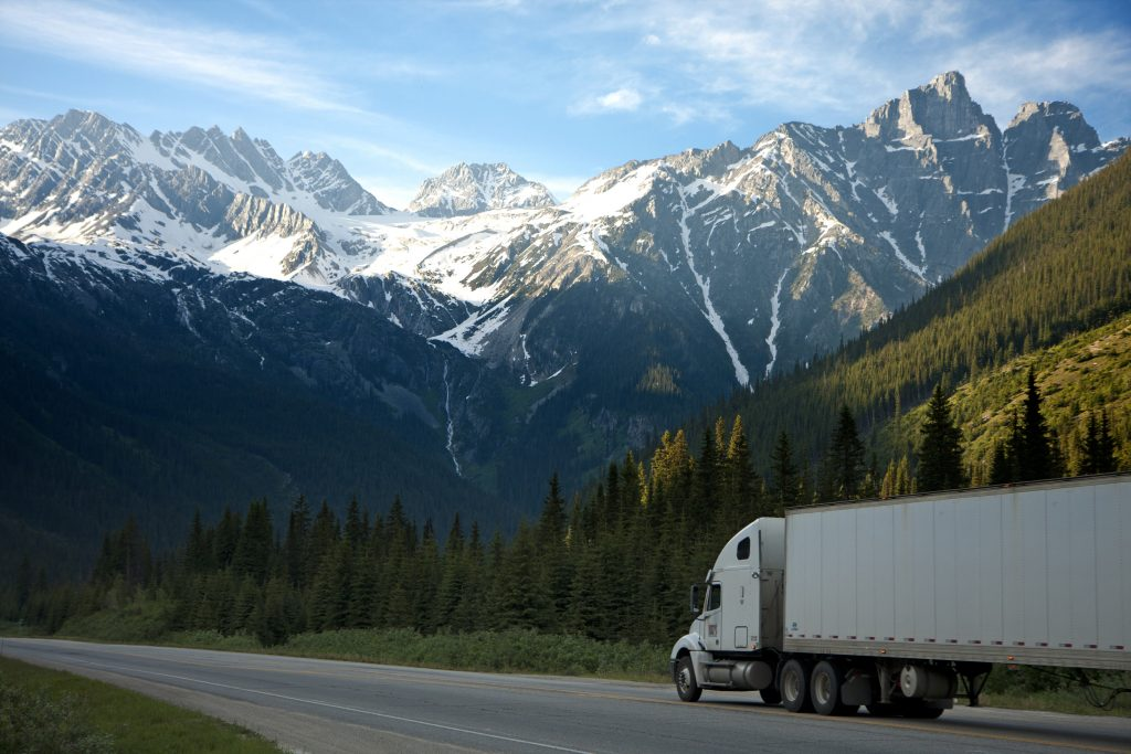 A truck drives down the road against a mountainous background