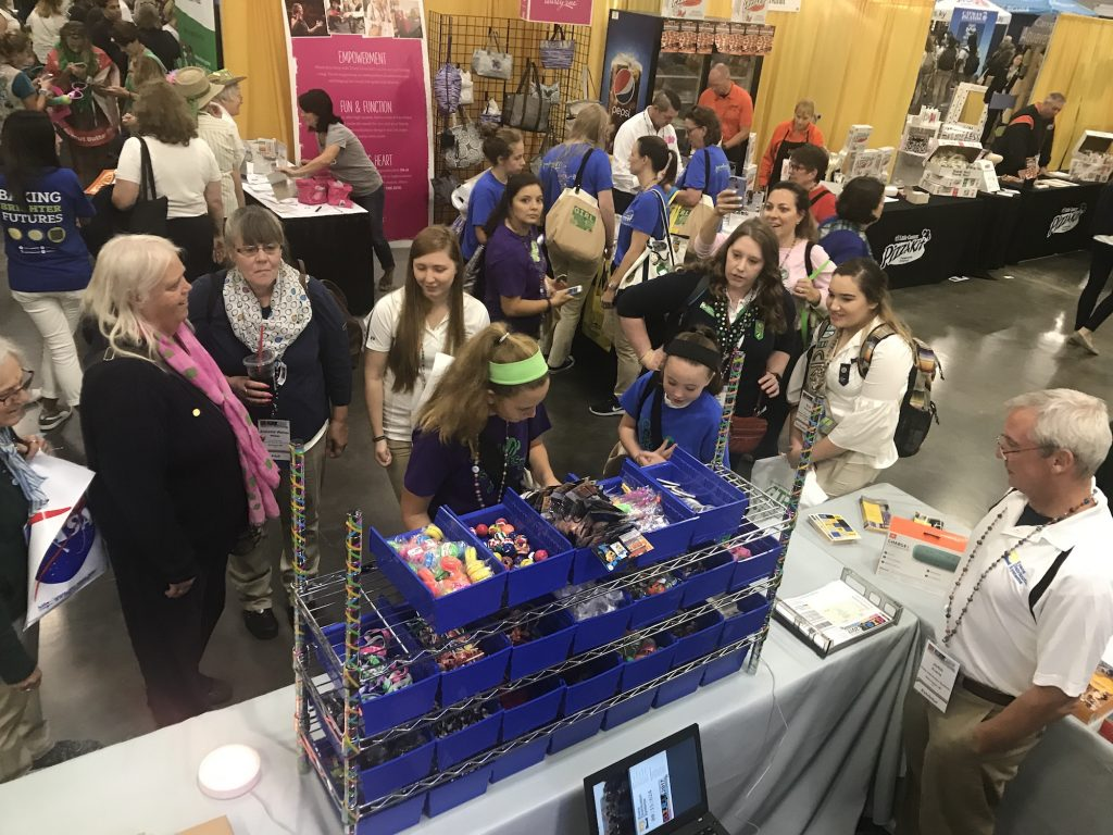 Group of girl scouts stands around pick and pack station at the GIRL convention.