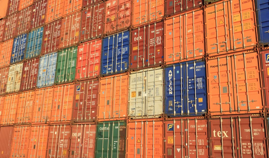 Many crates stacked on top of each other at an ocean port