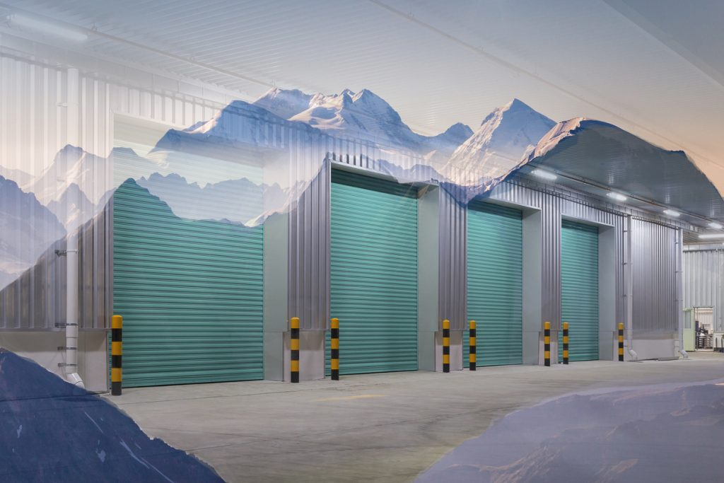 Warehouse doors interlinked with a mountaintop, which borders the top of the doors.