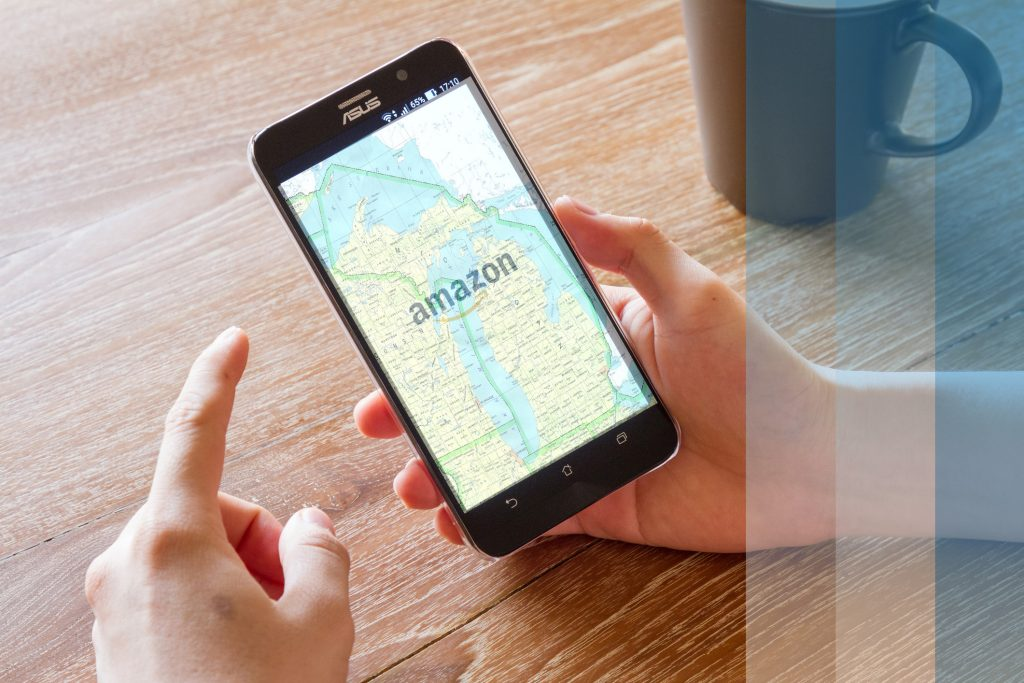 Hand holding phone. On the screen is the amazon logo, superimposed over a map of Michigan.